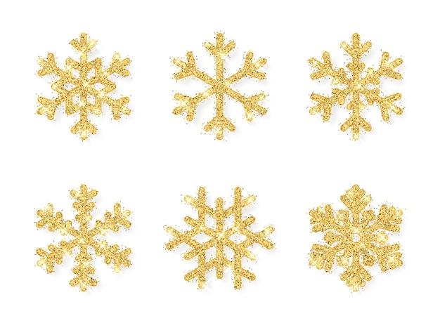 Błyszczące złote płatki śniegu na białym tle. boże narodzenie i nowy rok tło.