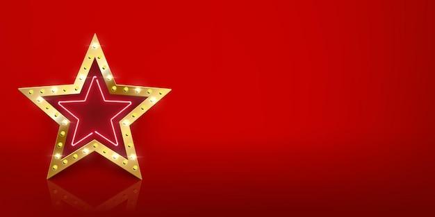 Błyszczący złoty znak gwiazdy z żarówkami i neonem z lustrzanym odbiciem na czerwonym tle