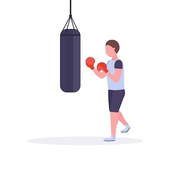Bokser człowiek robi ćwiczenia z workiem treningowym co bezpośrednie uderzenie w czerwone rękawice bokserskie facet wojownik szkolenia trening zdrowego stylu życia koncepcja białe tło