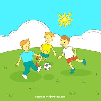 Boys gry w piłkę nożną na polu