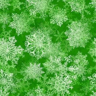 Boże narodzenie bezszwowe wzór dużych złożonych płatków śniegu w kolorach zielonym. zimowe tło ze spadającym śniegiem