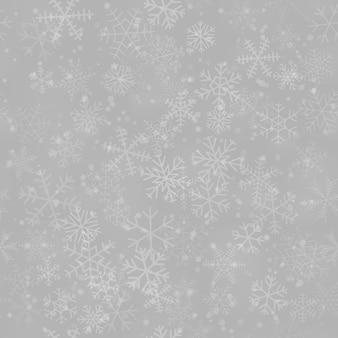 Boże narodzenie bezszwowe wzór płatków śniegu o różnych kształtach, rozmiarach i przezroczystości, na szarym tle