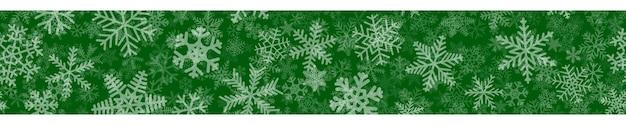 Boże narodzenie poziomy bezszwowe transparent z wielu warstw płatków śniegu o różnych kształtach, rozmiarach i przezroczystości. biały na zielonym.