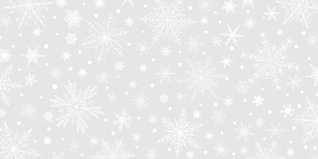 Boże narodzenie tło różnych złożonych dużych i małych płatków śniegu, biały na szarym