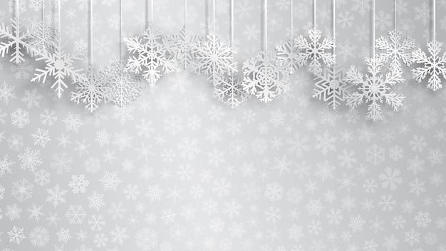Boże narodzenie tło z dużymi białymi wiszącymi płatkami śniegu na szarym tle małych płatków śniegu