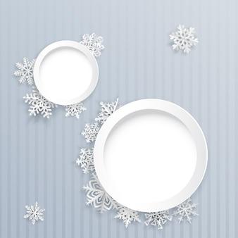 Boże narodzenie tło z dwiema okrągłymi ramkami i papierowymi płatkami śniegu na szarym tle w paski