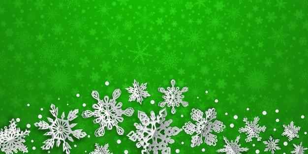 Boże narodzenie tło z objętościowymi płatkami śniegu z miękkimi cieniami na zielonym tle