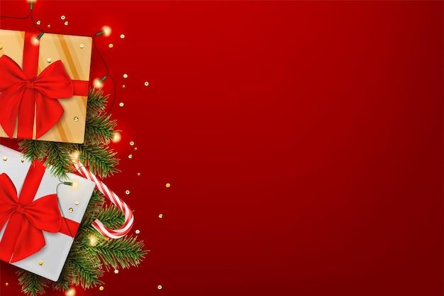 Boże narodzenie tło z realistyczną wstążką pudełko prezentów i gałęziami sosny.