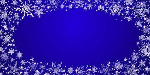Boże narodzenie tło z różnymi złożonymi dużymi i małymi płatkami śniegu, białe na niebieskim, ułożone w elipsę