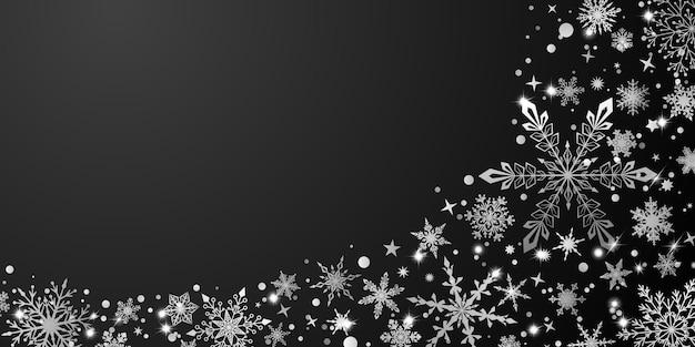 Boże narodzenie tło z różnymi złożonymi dużymi i małymi płatkami śniegu, biały na czarnym