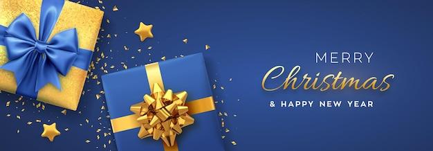 Boże narodzenie transparent. realistyczne pudełka prezentowe ze złotymi i niebieskimi kokardkami, złotymi gwiazdkami i brokatowym konfetti. boże narodzenie tło, poziomy plakat bożonarodzeniowy, kartki okolicznościowe, nagłówki strony internetowej. ilustracja wektorowa.