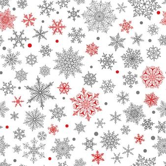 Boże narodzenie wzór dużych i małych złożonych płatków śniegu w kolorach czarnym, czerwonym i białym. zimowe tło ze spadającym śniegiem