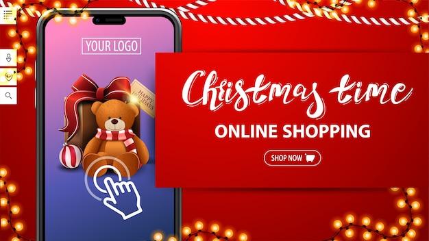 Boże narodzenie, zakupy online, czerwony baner rabatowy z dużym smartfonem z prezentem na ekranie. baner rabatowy na twoją stronę internetową