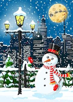Boże narodzenie zimowy pejzaż miejski, bałwan i drzewa. aleja śnieżna w parku miejskim i budynki.