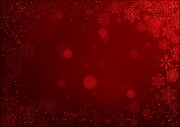 Bożenarodzeniowi płatki śniegu na czerwonym bokeh tle