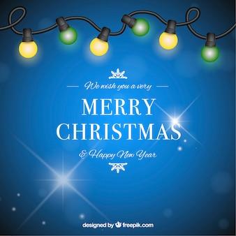 Bożenarodzeniowy tło w błękicie z żółtymi i zielonymi bożonarodzeniowe światła