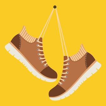 Brązowe buty wiszą na sznurowadłach