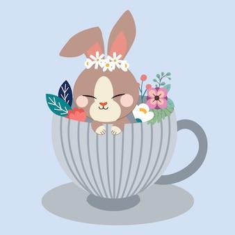 Brązowy królik siedzi w dużej filiżance i ślicznym kwiacie.