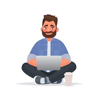 Brodaty mężczyzna siedzi na podłodze i pracuje przy laptopie. praca zdalna przez internet. wolny strzelec.