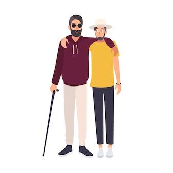 Brodaty niewidomy mężczyzna w okularach przeciwsłonecznych i lasce stoi i obejmuje się ze swoim przyjacielem
