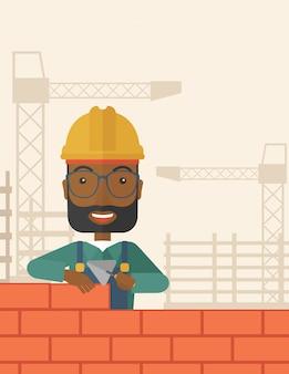 Budowniczy czarny człowiek buduje mur z cegły.