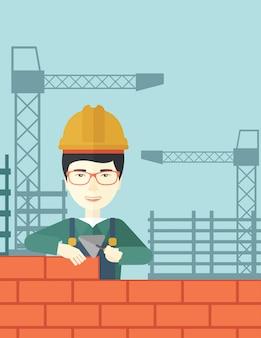 Budowniczy człowiek buduje mur z cegły.