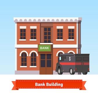 Budynek banku z ciężarówką pancerną z przodu