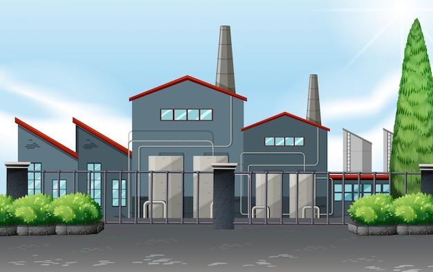 Budynek fabryczny za metalowym ogrodzeniem
