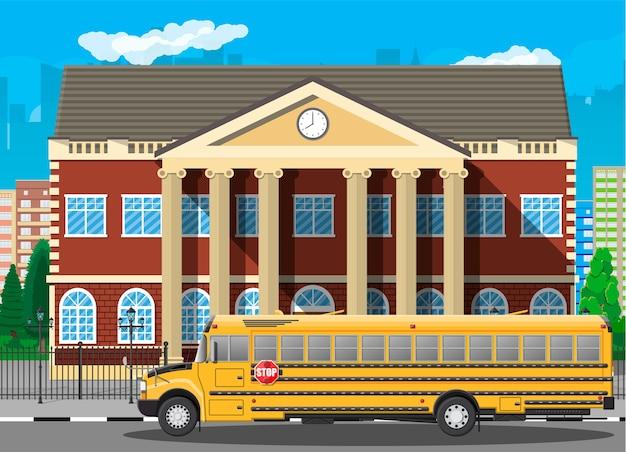 Budynek szkoły klasycznej i pejzaż miejski. ceglana fasada z zegarami. publiczna instytucja edukacyjna i autobus. uczelnia lub organizacja uniwersytecka. drzewo, chmury, słońce.