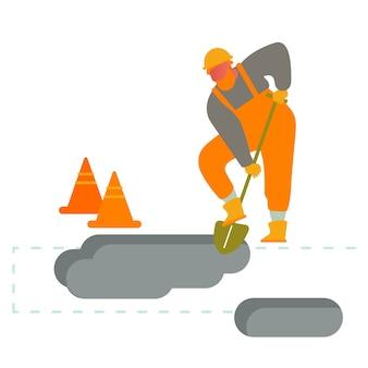 Builder kopanie ziemi za pomocą łopaty.