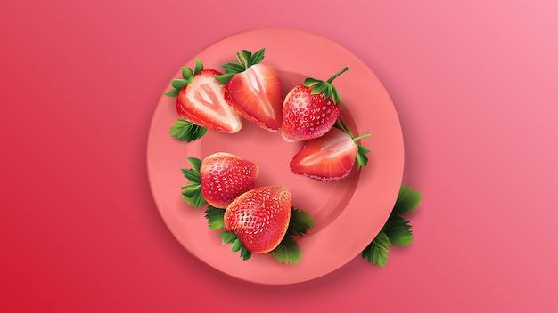 Całe i pokrojone truskawki na różowym talerzu.