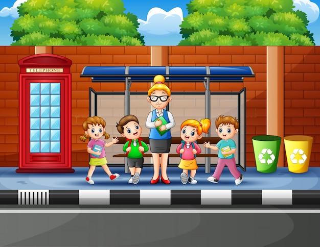 Cartoon dzieci w wieku szkolnym na przystanku autobusowym z nauczycielem