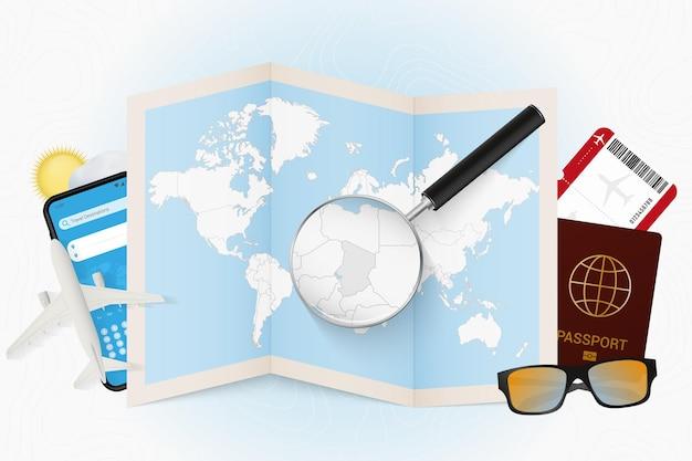 Cel podróży czad, makieta turystyki z wyposażeniem podróży i mapa świata z lupą na czadzie.