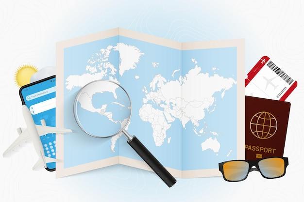 Cel podróży gwatemala, makieta turystyki z wyposażeniem podróży i mapa świata z lupą na gwatemali.