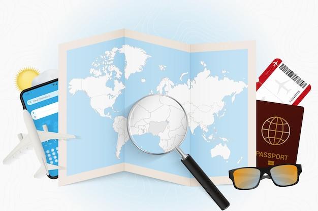 Cel podróży nigeria, makieta turystyki z wyposażeniem podróży i mapa świata z lupą na nigerii.