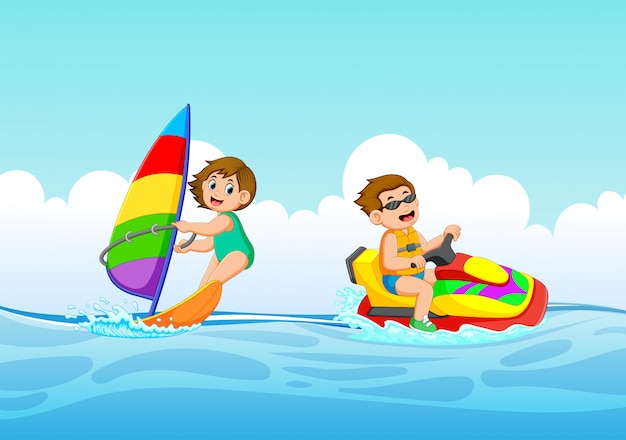 Chłopak i dziewczyna bawią się na skuterach wodnych i łodziach żaglowych