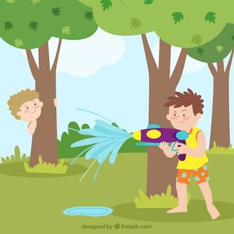 Chłopcy bawiący się pistoletami na wodę w parku