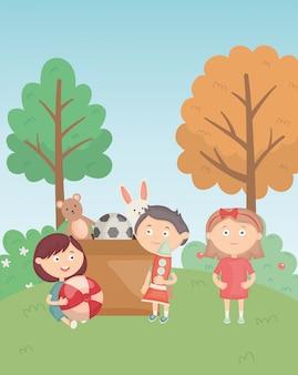 Chłopcy i dziewczyny z pudełkiem i zabawkami w parku