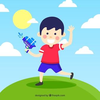 Chłopiec bawi się niebieski pistolet wody