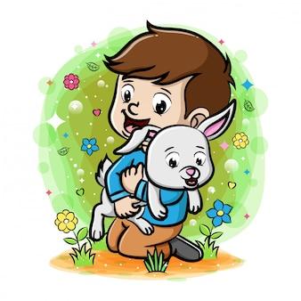 Chłopiec bawi się z królika w ogrodzie