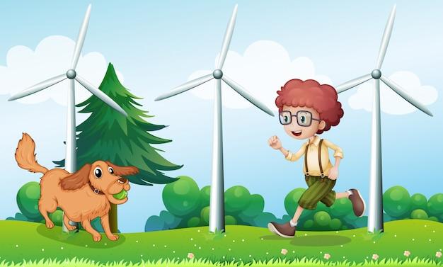 Chłopiec bawi się z psem w pobliżu wiatraka