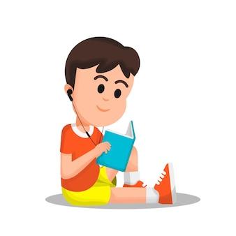 Chłopiec czytający książkę ze słuchawkami w uchu