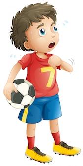 Chłopiec gra w piłkę nożną, patrząc zmęczony