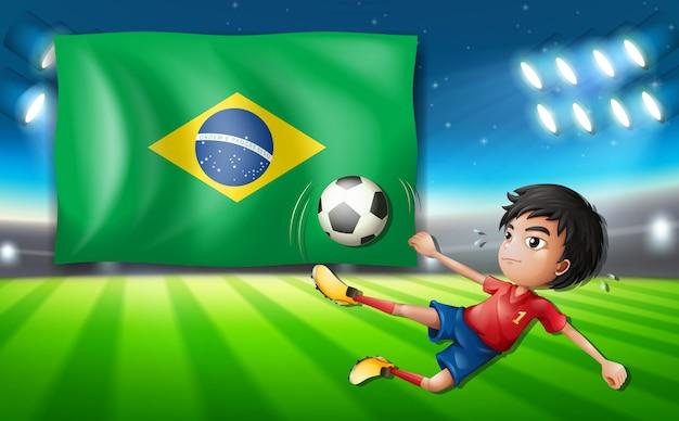 Chłopiec gracz piłki nożnej przed brazil flaga