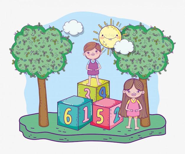 Chłopiec i dziewczyna z sześcianami gra i słońce