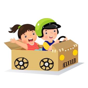 Chłopiec i dziewczynka jeżdżą tekturowym samochodem