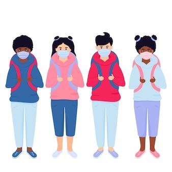 Chłopiec i dziewczynka noszą maskę chroniącą przed wirusem. dzieci z plecakami i książkami gotowe do powrotu do szkoły.