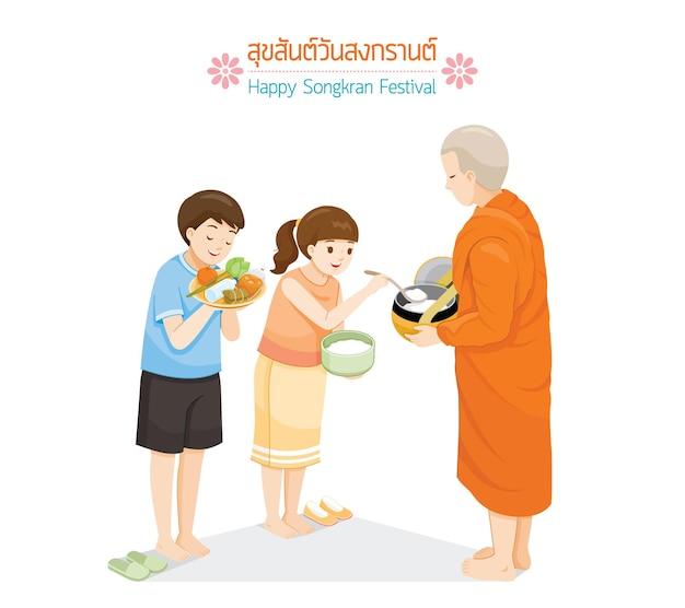 Chłopiec i dziewczynka ofiarowują jedzenie w misce jałmużny mnichowi tradycja tajski nowy rok suk san wan songkran przetłumacz happy songkran festival
