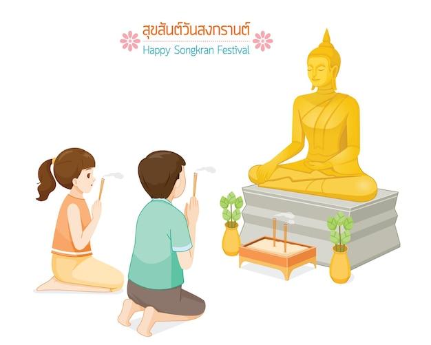 Chłopiec i dziewczynka okazują szacunek posągowi buddy lekkimi kadzidełkami tradycja tajski nowy rok suk san wan songkran przetłumacz happy songkran festival