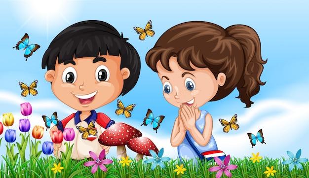 Chłopiec i dziewczynka w ogrodzie pełnym motyli
